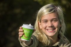 Cheerful girl. Holds a coffee Cup with the inscription `Enjoy Royalty Free Stock Photos