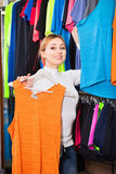 Cheerful  girl choosing a t-shirt in the store Royalty Free Stock Photos