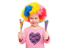 Cheerful girl with clown wig. Is playing with bright toys Stock Photography
