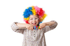 Cheerful girl in clown wig. Plays with toys Royalty Free Stock Photography
