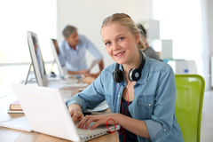 Cheerful girl in computing class using laptop royalty free stock images