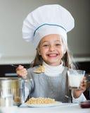 Cheerful girl in cook cap eating porridge indoors Stock Photography