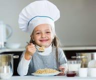 Cheerful girl in cook cap eating porridge indoors Royalty Free Stock Image