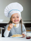 Cheerful girl in cook cap eating porridge indoors Royalty Free Stock Photos