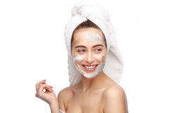Cheerful girl with cosmetics and towel. Horizontal studio shot of smiling young woman applying different cosmetics isolated on white Royalty Free Stock Photo