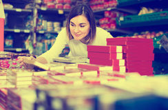 Cheerful girl customer looking for tasty sweets in supermarket Royalty Free Stock Photography
