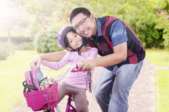 Cheerful girl and dad with bicycle at the park Stock Image