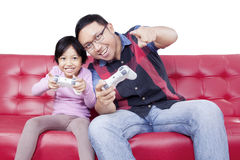 Cheerful girl and dad playing video game Stock Photography