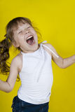 Cheerful girl dances on a yellow background Stock Images
