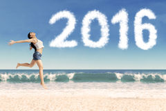 Cheerful girl dancing at coast with numbers 2016 Stock Image
