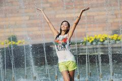 Cheerful girl dancing under jets of water in city fountain Royalty Free Stock Image