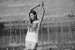 Cheerful girl dancing under jets of water in city fountain Stock Photo