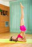 Cheerful girl doing yoga at home Stock Images