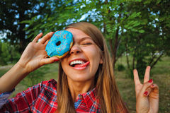 Cheerful girl and a donut Stock Photography