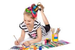 Cheerful girl draws lying on the floor Stock Photography