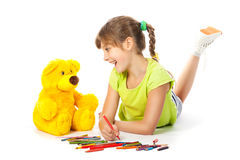 Cheerful girl draws pencil Stock Images