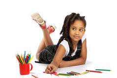 Cheerful girl draws pencil lying on the floor. Happy girl draws and writes lying on the floor Isolation on white background Stock Image