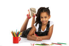 Cheerful girl draws pencil lying on the floor Stock Photos