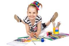 Cheerful girl draws pencil lying on the floor Royalty Free Stock Photos