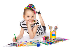Cheerful girl draws pencil lying on the floor Royalty Free Stock Photos