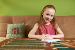Cheerful girl in  dress draws pencils Royalty Free Stock Image