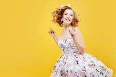 Cheerful girl in dress and headband with bow, pin up style. royalty free stock photos