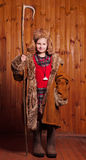 Cheerful girl dressed in a coat wearing boots and took the staff. Shepherdess. Royalty Free Stock Images