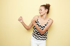 Cheerful girl dressed in a striped top and white jeans happily dancing on the yellow background in the studio royalty free stock photo