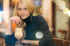 Cheerful girl drinking coffee in a cafe Stock Image