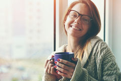 Cheerful girl drinking coffee or tea Stock Images