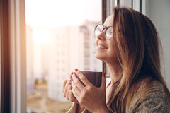 Cheerful girl drinking coffee or tea Royalty Free Stock Images