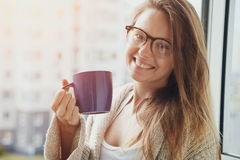 Cheerful girl drinking coffee or tea Stock Image