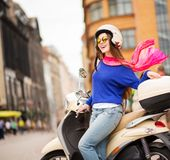 Cheerful girl driving scooter Stock Images