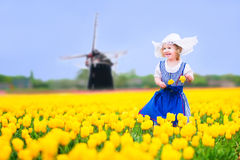 Cheerful girl in Dutch costume in tulips field with windmill. Adorable curly toddler girl wearing Dutch traditional national costume dress and hat playing in a Stock Images