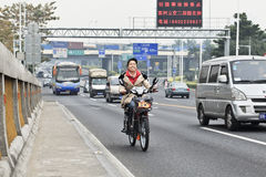 Cheerful girl on an electric bike on the road, Guangzhou, China. GUANGZHOU-FEB. 21, 2012. Air pollution on Feb. 21, 2012 in Guangzhou. China has surpassed the Royalty Free Stock Images