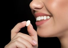 Cheerful girl is enjoying chicle. Close up side view of young positive woman is putting chewing gum into her mouth. Fresh breath concept. Isolated on dark Royalty Free Stock Photo