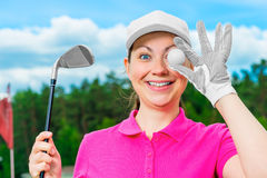 Cheerful girl with the equipment for golf. Cheerful girl in a baseball cap with the equipment for golf Stock Photo