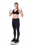Cheerful girl excited with results as she lost weight. Girl standing on weighing scale and showing thumbs up sign Royalty Free Stock Image