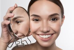 Cheerful girl is expressing gladness. Natural attractiveness. Close up portrait if positive delighted young woman is standing and holding mirror near her face royalty free stock photo