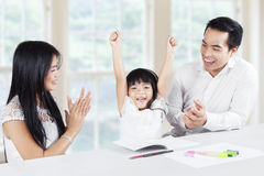 Cheerful girl finishing homework and get applause. Image of a little girl finishing homework and get applause from her parents at home stock photo