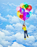 Cheerful girl flies with balloons Stock Photo