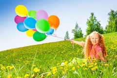 Cheerful girl with flying balloons sits on grass Royalty Free Stock Photos