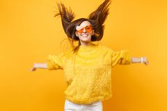 Cheerful girl in fur sweater, heart orange glasses fooling around in studio jump with flowing hair isolated on bright royalty free stock image