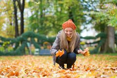 Cheerful girl gathering autumn leaves Royalty Free Stock Photo