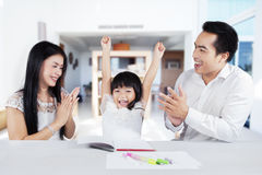 Cheerful girl get appreciation from her parents Stock Images