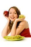 Cheerful girl with grapes and an apple Royalty Free Stock Photography