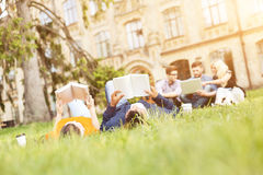 Cheerful girl and guys resting in campus. Enjoying university life. Cute young students are lying on grass. Man and women are reading book with relaxation. Their Stock Images
