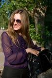 Cheerful girl with a handbag and dark glasses Royalty Free Stock Photos