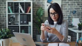 Cheerful girl happy employee using smartphone touching screen working in office stock footage