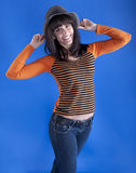 Cheerful girl in a hat on a blue background stock photography